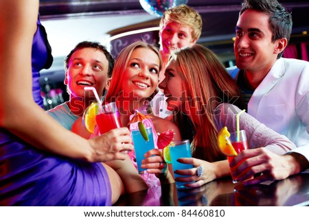 Photo of pretty girls and guys looking at one of their friends sitting on the bar