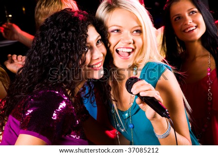 Photo of pretty girls with microphone singing in it