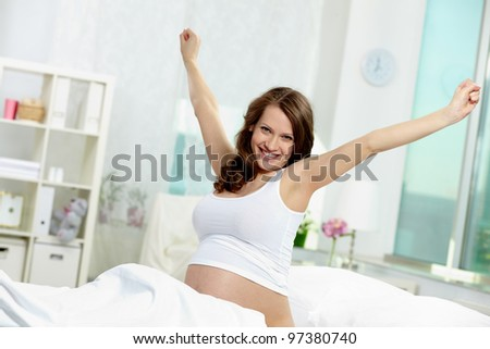 Photo of pretty pregnant woman in bed looking at camera - stock photo