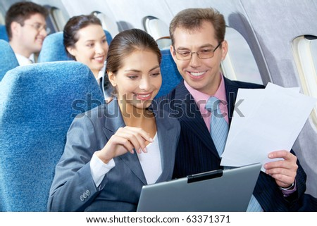 Photo of pretty woman communicating with handsome partner sitting next to her in airplane