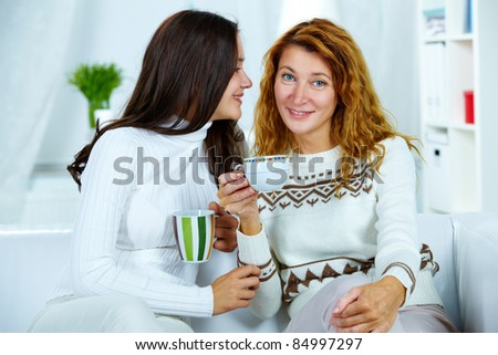 Photo of pretty woman looking at camera with her teenage daughter near by - stock photo