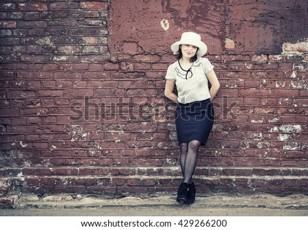 Photo of pretty young woman in white hat, blouse and black skirt, posing against brick wall background. Woman is leaning against the wall. Toned photo with copy space. Vintage style photo. - stock photo