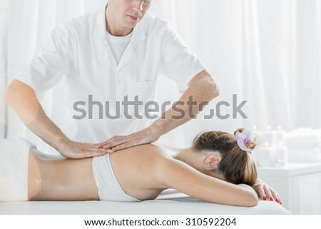 Photo of professional male masseur massaging womans back - stock photo