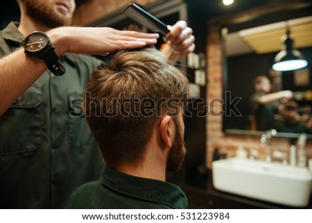 Photo of professional stylist cut hair of his client. Back view.