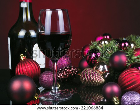 Photo of romantic Christmas dinner, glass of red wine, beautiful little candle, holiday table setting, New Year decorations on a mirrored table with red background.  - stock photo