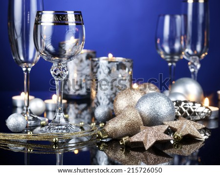 Photo of romantic Christmas dinner, several glasses, beautiful little candle, gold shiny bauble, holiday table setting, New Year decorations on a mirrored table with blue background.  - stock photo