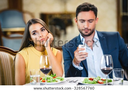 Photo of romantic dinner in expensive hotel. Young woman is bored and lonely while her boyfriend using mobile phone - stock photo