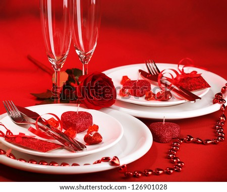 Photo of romantic dinner table setting, holiday banquet, white festive dinnerware on red tablecloth decorated with fresh rose flower and heart-shaped candles, Valentine day, two wineglasses - stock photo