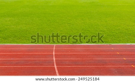 Photo of running track with green grass - stock photo