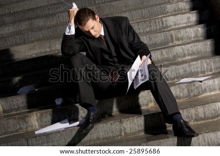 Photo of sad man with papers in hands sitting on stairs with no idea what to do