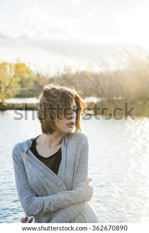 photo of sad redhead teenager girl at the lake. Freeze Woman stand against sunset sky with clouds