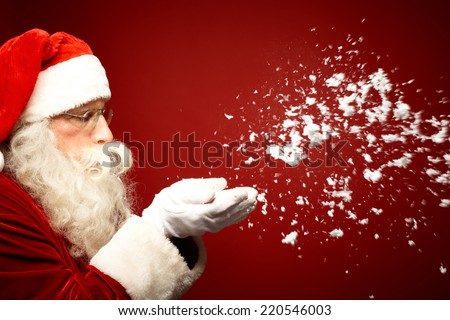 Photo of Santa Claus blowing snow over red background