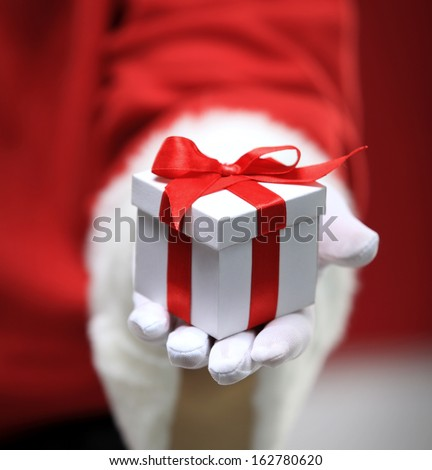 Photo of Santa Claus gloved hands holding white giftbox - stock photo