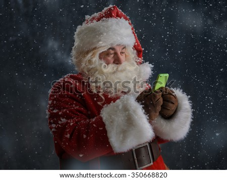 Photo of Santa Claus using mobile phone outdoors under snow  - stock photo
