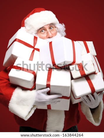 Photo of Santa Claus with giftboxes looking at camera  - stock photo