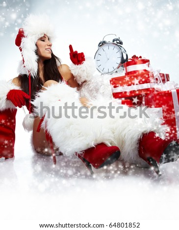 Photo of Santa girl pointing at clock showing five minutes to midnight - stock photo