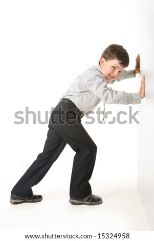Photo of schoolboy standing near white wall and setting against it - stock photo