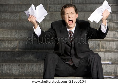 Photo of screaming businessman with two sheets of paper in his hands - stock photo