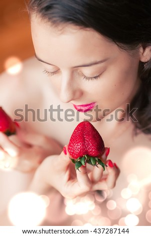 Photo of seductive female eating strawberry, closeup portrait of  sensual woman biting juicy fruit , fruity diet, tasty dessert, Valentine day, pleasure concept - stock photo