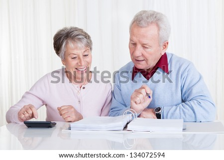 Photo of Senior Couple Calculating Budget At Home