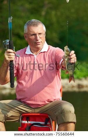 Photo of senior man catching fish on weekend - stock photo