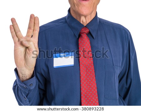 "Photo of senior man in a blue shirt and red tie wearing a ""Hello My Name Is"" name tag and giving the hand signal to ""live long and prosper."" - stock photo"