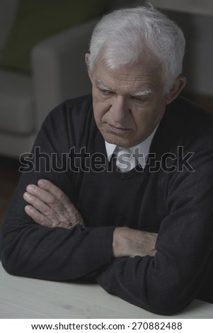 Photo of senior man with depression sitting alone - stock photo