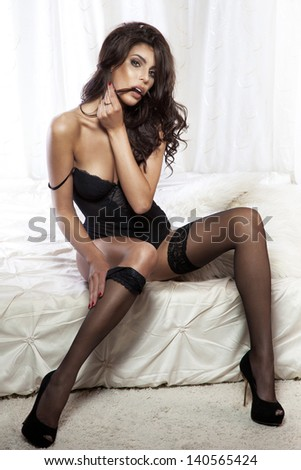 Photo of sensual beautiful brunette woman sitting on bed wearing elegant black lingerie. - stock photo