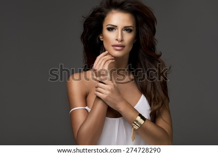 Photo of sensual beautiful woman looking at camera, posing in white top.
