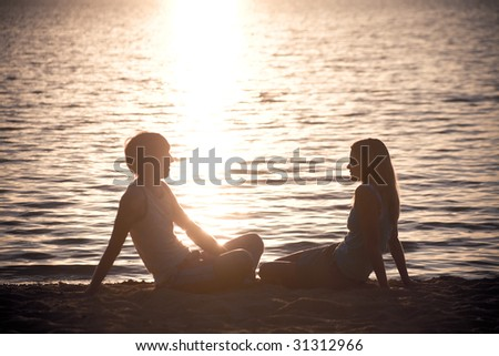 Photo of serene couple sitting on the seashore and talking at sunset - stock photo