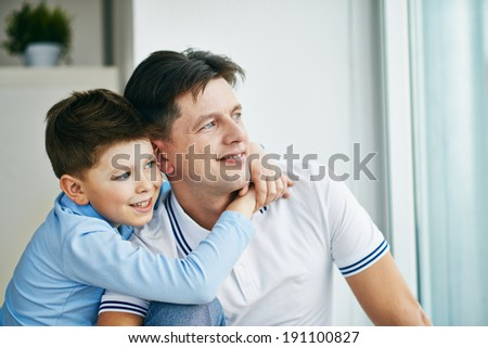 Photo of serene man and his son looking through window