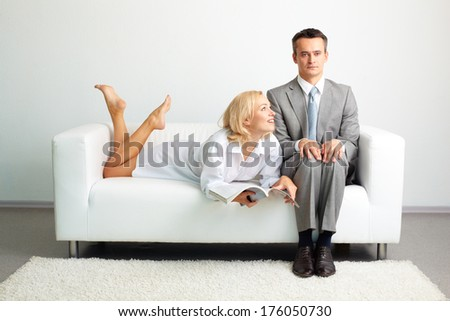 Photo of serious man sitting on sofa with happy woman with magazine lying near by - stock photo