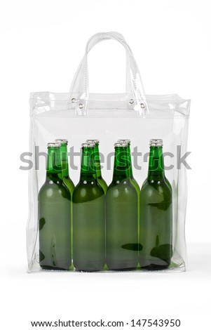 Photo of several cold beers in a transparent plastic bag, with working path. The beers are in green bottles and in  colorless bag isolated on white background.  - stock photo