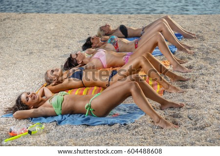 Photo Of Several Girls In Bikini Lying On Sandy Beach And Tanning The Bright Summer