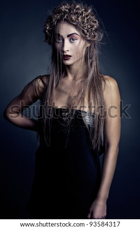 Photo of sexy beautiful woman with magnificent hair posing on dark background - stock photo
