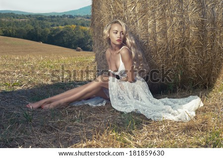Photo of sexy blonde in a field with haystacks - stock photo