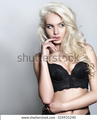 Photo of sexy blonde young girl in a black bustier, posing in studio. - stock photo