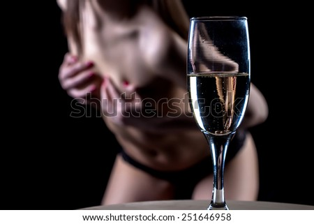 Photo of sexy woman behind the glass on black background - stock photo