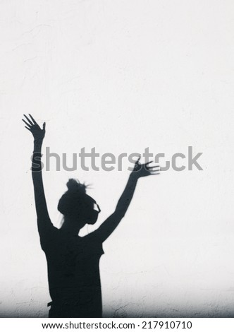 Photo of shadows of dj girl with headphones lifting her hands up.