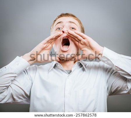 Photo of shouting man with his palms open by mouth looking upwards - stock photo