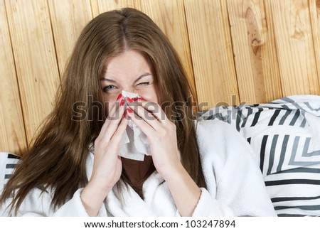 Photo of sick woman sitting in bed with tissue and blowing her nose into it - stock photo