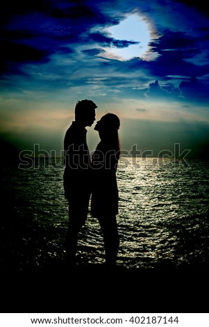 photo of silhouette of sweet couple with sunset at the sea. - stock photo