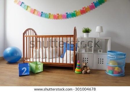 Photo of simple design wooden cradle in cosy baby bedroom - stock photo
