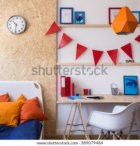 Photo of single bed with decorative cushions in teenager room - stock photo