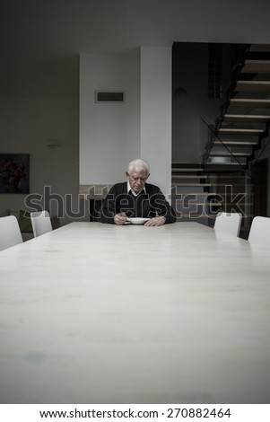 Photo of single older man eating dinner alone at home - stock photo