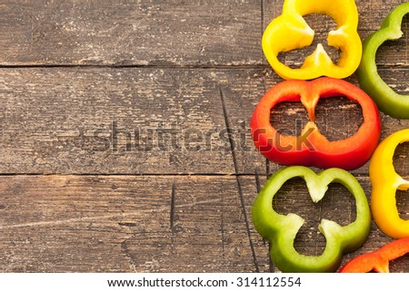 Photo of sliced colorul peppers over wooden table - stock photo