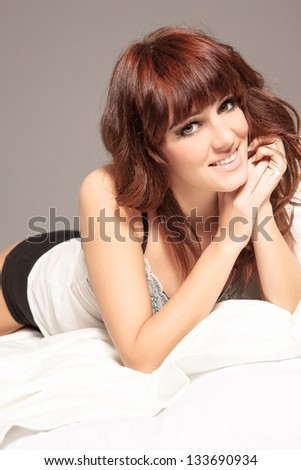 photo of smiling brunette wearing lingerie in her bed