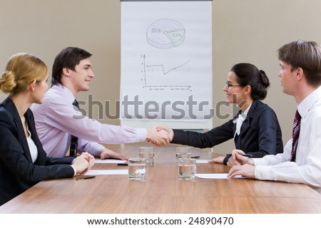 Photo of smiling business partners handshaking after striking successful deal