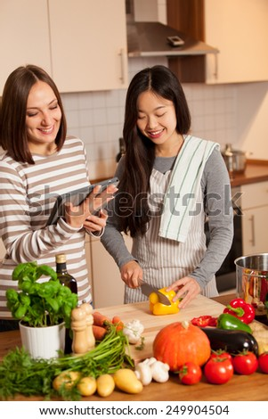 photo of smiling female friends cooking in the kitchen at home - stock photo