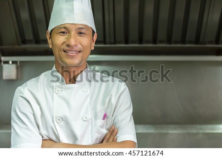 Photo of smiling man standing in the kitchen chef, Chef Thailand - stock photo